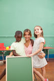 Teacher with her students holding a blackboard Royalty Free Stock Photos