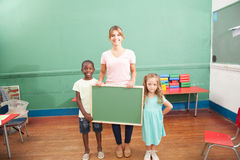 Teacher with her students holding a blackboard Royalty Free Stock Images