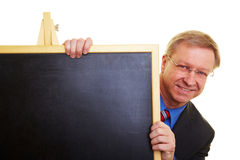 Teacher hiding behind blackboard Stock Photo