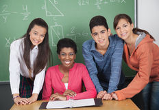 Teacher With High School Students At Desk Royalty Free Stock Images