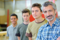 Teacher with his students lined up beside him Stock Image