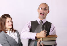 Teacher hold textbooks. Mad teacher holding books and  screaming loud at the camera and teen age girl making disappointing face looking at him Royalty Free Stock Photography