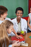 Teacher Holding Apple With Students Standing At Stock Photography