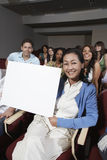 Teacher Holding Billboard With Students In The Background royalty free stock photos