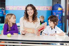 Teacher Holding Book With Children At Desk. Beautiful teacher looking away while holding book with children at desk in classroom Stock Image