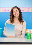 Teacher Holding Book While Sitting At Desk Stock Image