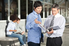 Teacher Holding Books While Discussing With. Mature male teacher holding books while discussing with student on college campus royalty free stock image