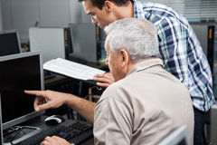 Teacher Holding Clipboard While Assisting Senior Man In Using Co Royalty Free Stock Photography