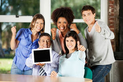 Teacher Holding Digital Table With Students. Portrait of happy male teacher holding digital table with students gesturing in classroom Stock Photos