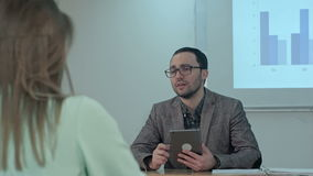 Teacher holding digital tablet in hands while teaching lessons in school classroom to students stock footage