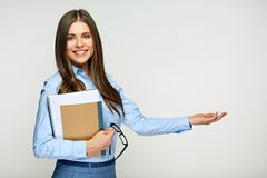 Teacher holding exercise books and presenting empty hand for pr. Smiling woman teacher holding exercise books and presenting empty hand for product. Portrait stock images
