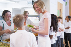 Teacher holding plate of lunch in school cafeteria Royalty Free Stock Photo