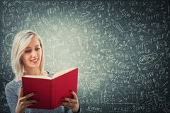Solve equation. Teacher holding a red book in front of a huge blackboard try to solve hard mathematics calculation, formula and equations. Thinking of project royalty free stock images