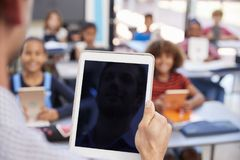 Teacher holding tablet in school class, over shoulder view Stock Photography