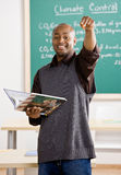 Teacher holding text book pointing to student