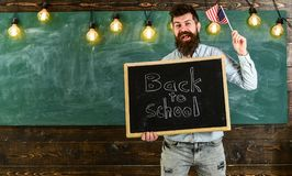 Teacher holds blackboard with written phrase back to school and flag of USA. American school concept. Man with beard on. Smiling face welcomes to american Stock Photography