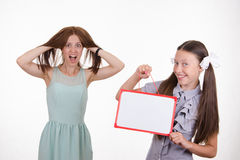 Teacher in horror, student with a sign Royalty Free Stock Photo