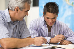 A teacher instructs a schoolboy Stock Photography