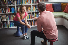 Teacher interacting with student in library. At school Stock Photo