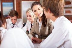 Teacher interacting with students. High school teacher interacting with students in classroom Stock Photos
