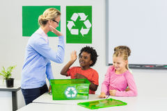 Teacher and kids giving high five to kids. In classroom Royalty Free Stock Photography