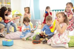 Teacher and cute kids during music lesson in preschool stock image