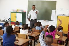 Teacher and kids with hands up in an elementary school class Stock Photography