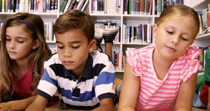 Teacher and kids lying on floor reading book in library. At elementary school stock video footage