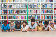 Teacher and kids lying on floor using digital tablet in library. At elementary school royalty free stock photo