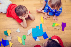 Teacher and kids playing with geometric shapes, early learning Stock Images