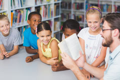 Teacher and kids reading book in library Stock Images