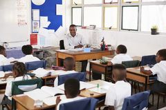 Teacher and kids sitting at desks in elementary classroom Stock Photography
