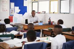 Teacher and kids sitting at desks in elementary classroom Royalty Free Stock Image