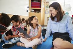 Teacher and kids sitting on the floor in elementary class royalty free stock images