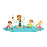 Teacher and kids sitting on the floor learning about plants during botany lesson, kids looking through magnifier Royalty Free Stock Photo