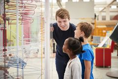 Teacher and kids talking about a science exhibit stock images