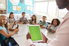 Teacher and kids using tablets in elementary school lesson royalty free stock photo