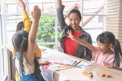 Teacher Kindergarten students hand up for happiness stock photos