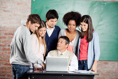 Teacher With Laptop Explaining Lesson To Students Stock Photography