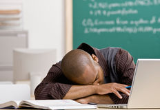 Teacher laying on desk in school classroom Royalty Free Stock Images