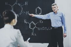Teacher Leading Lecture in University Classroom. Professor ask Student About Chemistry Formula. Educational Concept. Explanation for Students. Academic stock photos