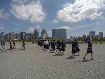 Teacher leading many of her students to see around Imperial Palace in sunny day stock image