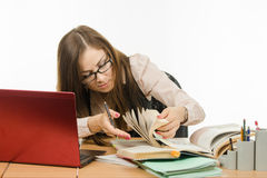 Teacher leafing through a book to find information Royalty Free Stock Image