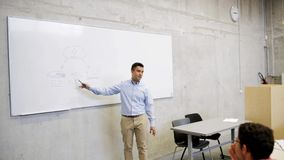 Teacher or lecturer at white board in lecture hall stock video