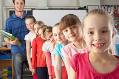 Teacher with line up of children in class. All looking at the camera Royalty Free Stock Photos