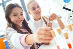 Teacher with little child in school laboratory new ingredient stock photos