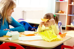 Teacher and little girl play with color paper Stock Image