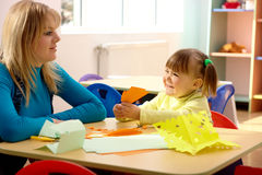 Teacher and little girl play with color paper Royalty Free Stock Photos