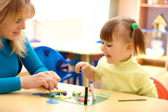 Teacher and little girl play with plasticine Stock Photos