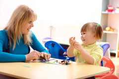 Teacher and little girl play with plasticine Stock Photo